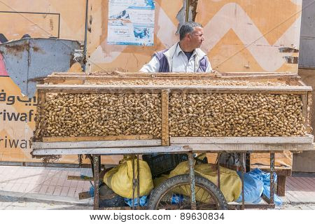 AS-SAWIRA, MOROCCO, APRIL 7, 2015: Seller of peanuts transports his mobile stand