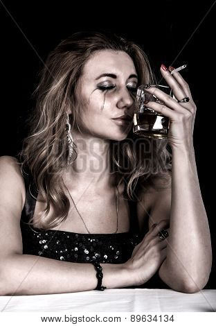 Depressed Young Woman With A Glass Of Whiskey And A Cigarette