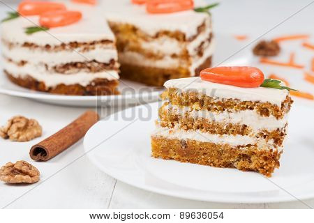 Delicious slice of carrot sponge cake with icing cream and little orange carrots