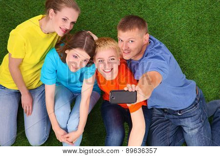 Group of young people sitting on green grass with  phone .
