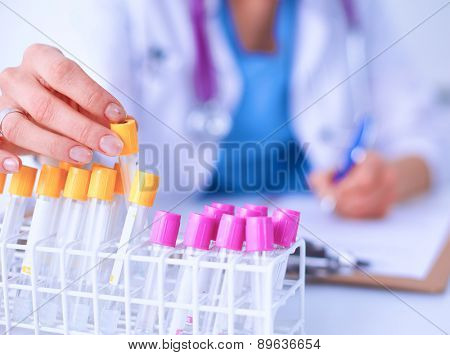 Woman researcher is surrounded by medical vials and flasks .
