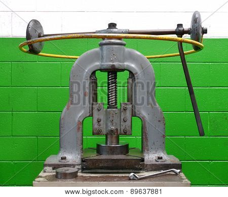 Vintage Manual Forming Press Against A Green Wall