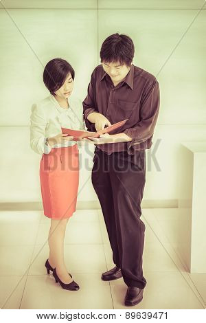 Thai (asian) Boss Is Ordering A Task For His Cute Secretary In The Office In Vintage Color