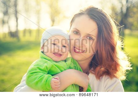 Young Happy Mother with Her Smiling Baby in Park