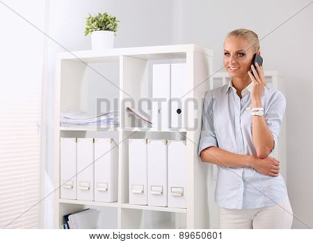Smiling businesswoman talking on the phone at the office.