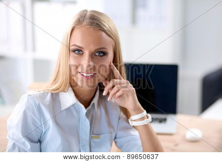 Portrait of beautiful young business woman working on a laptop.
