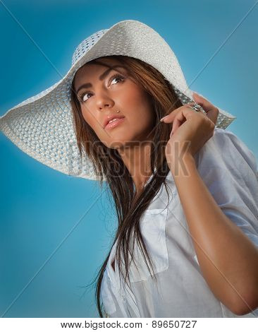 Portrait of attractive beautiful young woman with summer hat closeup, against blue sky