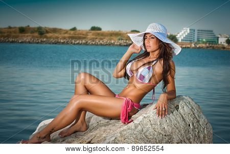 Full length portrait of young sexy brunette girl in bikini and big white hat at the beach