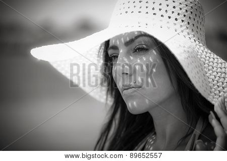 Black and white closeup portrait of attractive beautiful young woman wearing a large white hat