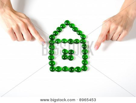 Beautiful Womans Hands Pointing Towards House Icon Made Of Little Stones