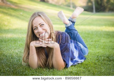 Portrait of a Beautiful Young Woman Laying in the Grass Outdoors at the Park.