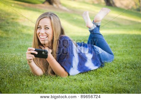 Smiling Young Woman Using Cell Phone Outdoors at the Park.