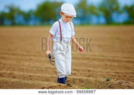 Cute Farmer Boy Walking The Arable Field