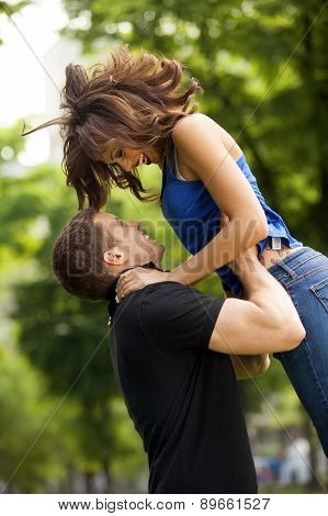Young couple in love, hugging, she is jumping,he is holding her in embrace