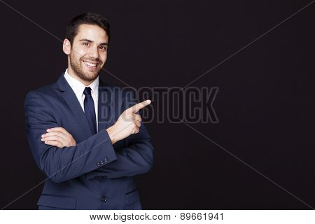 Handsome business man pointing at something against dark background