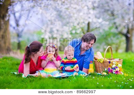 Young Family With Kids Having Picnic Outdoors