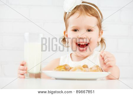 Happy Child  Girl Eats Cookies And Milk