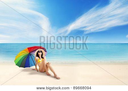 Female Tourist Sitting Under Umbrella
