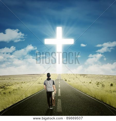 Male Guitarist With A Cross On The Road