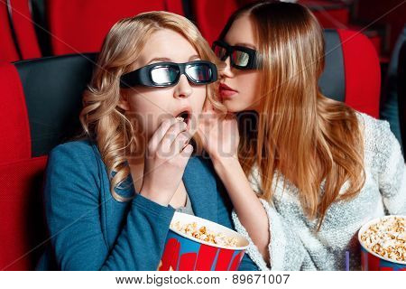 Woman sharing secret in cinema