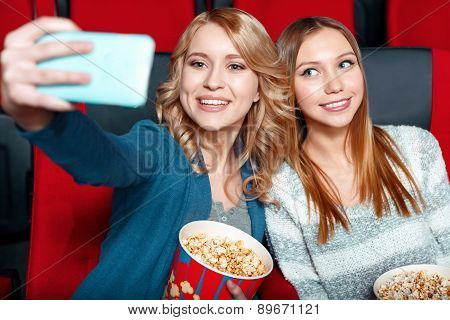 Two pretty girls doing selsie in cinema
