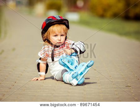 two year old pretty girl in roller skates and a helmet sitting on the street