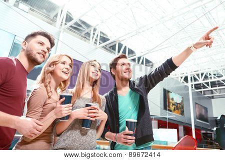 Group of people standing and pointing upwards