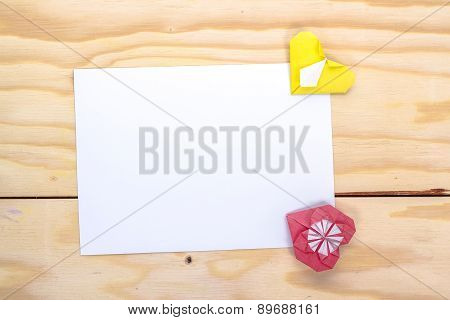 two origami hearts and white paper sheet for romantic message.