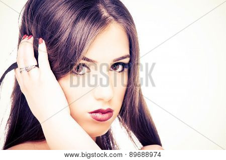 Beautiful young woman posing with her hand in a hair
