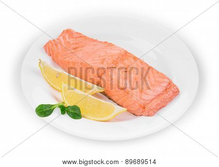 Fried salmon fillet on plate with lemon.