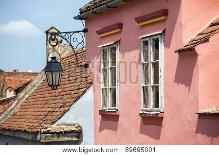 Pink Facade With White Windows And Street Lamp