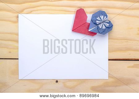 two origami hearts over white paper sheet.