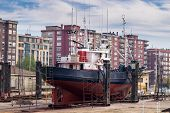 picture of shipyard  - Starboard view of a fishing boat in a shipyard for maintenance - JPG