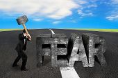 picture of overcoming obstacles  - Businessman holding sledgehammer hitting 3d fear mottled concrete word on asphalt road with sky clouds background overcoming fear concept - JPG