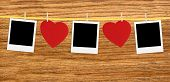 image of clotheslines  - Vintage photos frame on the clothesline with hearts over wooden background - JPG