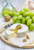 stock photo of brie cheese  - Soft brie cheese with sweet grapes and nuts closeup - JPG