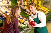 stock photo of grocery store  - woman in a supermarket at the vegetable shelf shopping for groceries - JPG