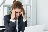 image of concentration  - Young beautiful business woman trying to concentrate looking at laptop monitor - JPG