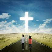 foto of rear-end  - Rear view of couple holding hands on the highway while looking at a cross on the end of the road - JPG