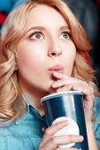 image of rapture  - Rapturous girl. Young blond woman enthusiastically watching film and drinking soda in cinema