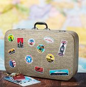 picture of cartographer  - retro suitcase with stikkers on the floor against the backdrop of a world map - JPG