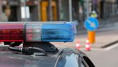 stock photo of flashing  - Blue and red flashing sirens of police car during the roadblock in the city - JPG