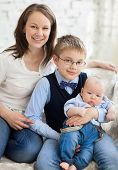 stock photo of nuclear family  - Happy mother with her children having fun in living room at home laughing - JPG