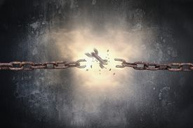 picture of slavery  - Rusty iron chains broken with red bright spark light on dark mottled concrete wall background - JPG