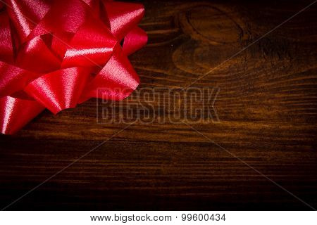 Tied bow - red ribbon on wooden planks