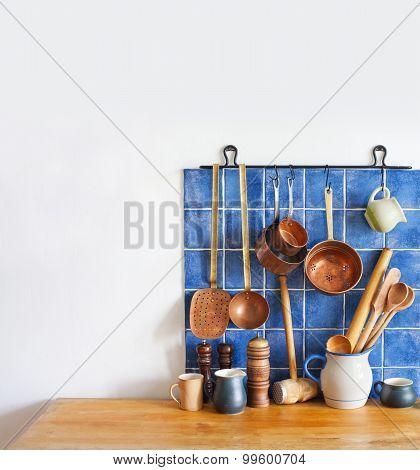 Kitchen Interior, Accessories. Hanging Copper Kitchenware Set. Spoon, Skimmer, Colander. Blue Tiles