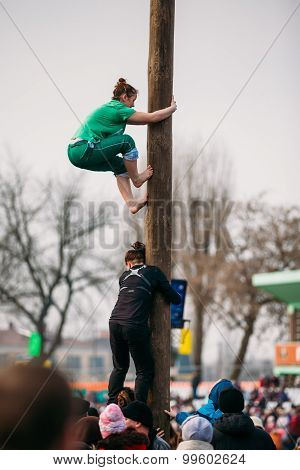 GOMEL, BELARUS - February 21, 2014: Young woman climbs on a wood