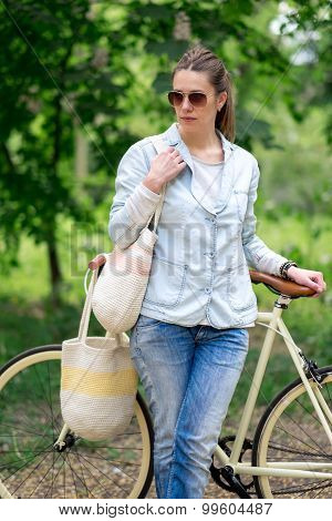 Beautiful Brunette Standing Near Her Yellow Bicycle