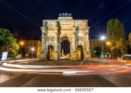 The Siegestor Victory Arch in Munich at dusk with traffic going around the arch.