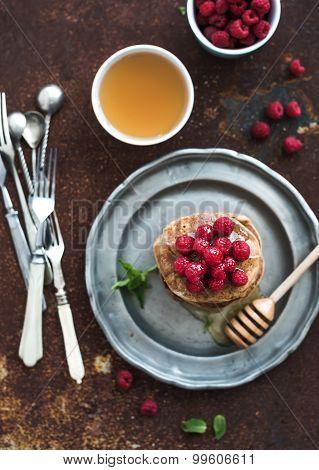 Breakfast set. Buckwheat pancakes with fresh raspberries, honey and mint leaves over grunge metal ba